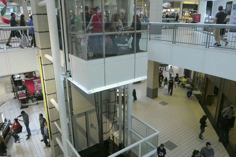 Christmas shoppers ride the elevator while others walk the floors at Ingram Park Mall on Black Friday, Nov. 27, 2015. General manager Tim Hill said renovations taking place at the mall won't impede shoppers.