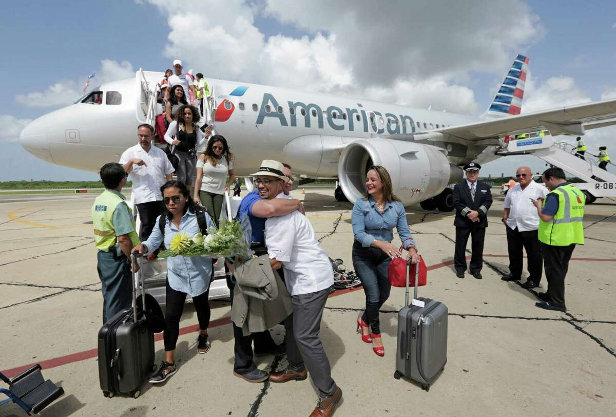 American Airline executive Gabriel Crespo greets travel agents on the tarmac as they arrive in Cienfuegos, Cuba on AmericanAirlines inaugural scheduled service from Miami to Cuba on Wednesday, Sept. 7, 2016. (Al Diaz/Miami Herald via AP)