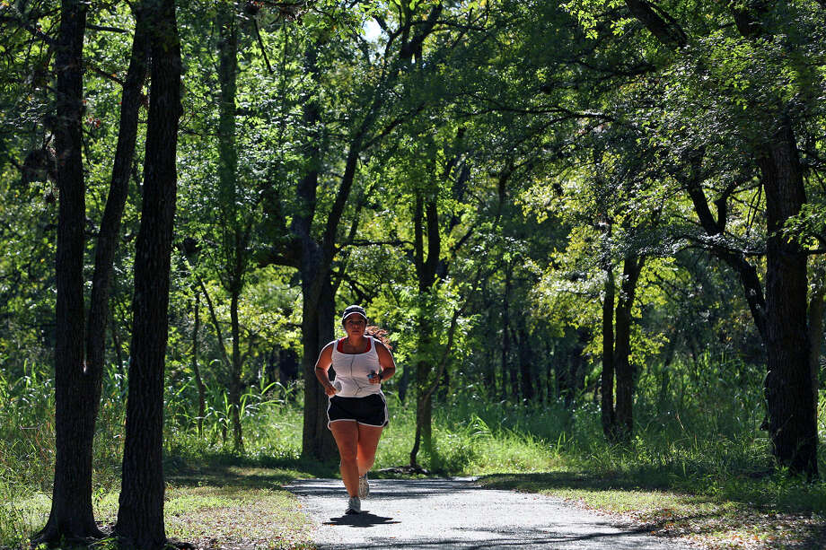 A jogger cruises into a sunny spot during her jog on the shady running pathways at McAllister Park. Photo: Express-News File Photo / treel@express-news.net