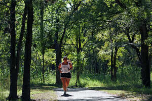 A jogger cruises into a sunny spot during her jog on the shady running pathways at McAllister Park.
