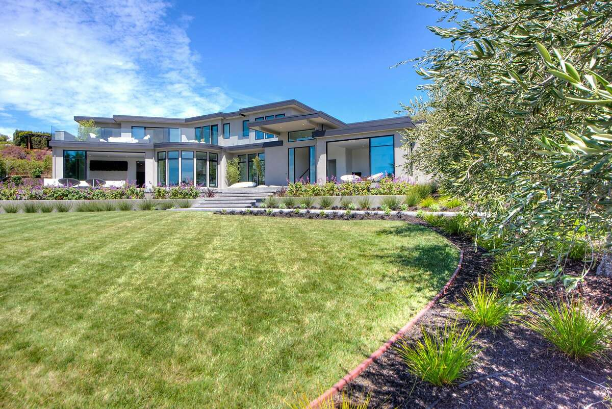 A large lawn stretches beyond the newly built luxury view home.