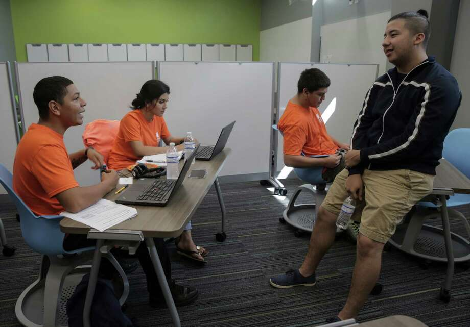 Simon Youth Academy students Manel Jicalan, 18, from left, his sister Andrea Jicalan, 17, Damien Rodriguez, 18, and David Alvarado, 19, chat while working on school work at the school located in the Katy Mills Mall on Thursday, Sept. 22, 2016, in Katy. The academy works on getting non-traditional students their diplomas. Photo: Elizabeth Conley, Houston Chronicle / © 2016 Houston Chronicle