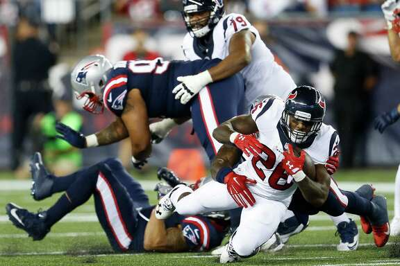 Houston Texans running back Lamar Miller (26) is tripped up by New England Patriots outside linebacker Jamie Collins (91) during the second quarter of an NFL football game at Gillette Stadium on Thursday, Sept. 22, 2016, in Foxborough, Mass.