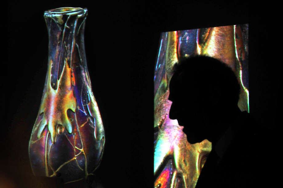 Art glass expert Paul Doros is silhouetted against the projected photos of a colorful and uniquely designed glass vase as he lectures on the work of famed artist Louis Comfort Tiffany at the McFaddin-Ward House Thursday night. Doros explored the character of the iconic glass art figure and what inspired his vision. Photo taken Thursday, September 22, 2016 Kim Brent/The Enterprise Photo: Kim Brent / Beaumont Enterprise