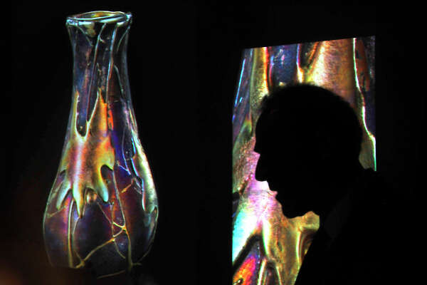 Art glass expert Paul Doros is silhouetted against the projected photos of a colorful and uniquely designed glass vase as he lectures on the work of famed artist Louis Comfort Tiffany at the McFaddin-Ward House Thursday night. Doros explored the character of the iconic glass art figure and what inspired his vision. Photo taken Thursday, September 22, 2016 Kim Brent/The Enterprise