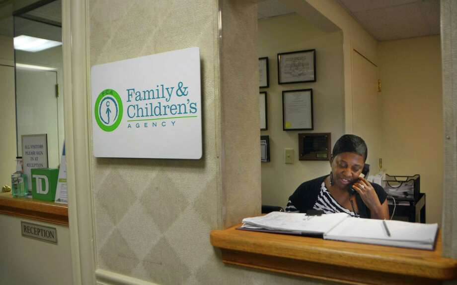 A staff member answers a phone call at the Family & Children's Agency in Norwalk last year. Photo: File Photo / Connecticut Post Freelance