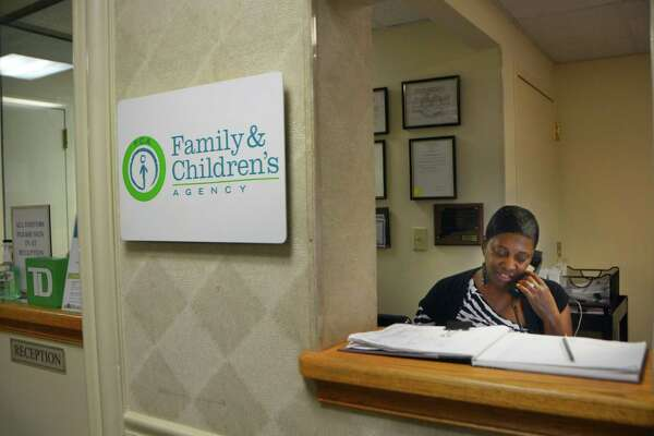 A staff member answers a phone call at the Family & Children's Agency in Norwalk last year.