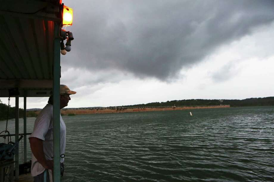 Mike Crandall of Wallys Water Sports peers across Medina Lake as a storm rolls into the area on May 31. Photo: Bob Owen /San Antonio Express-News
