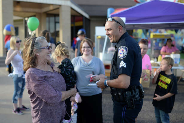 MPD Community Relations Sgt. Jimmy Young talks with Kelly Smith and 2-year-old Grace Wiggins during a National Night Out block party Tuesday, Oct. 6, 2015. James Durbin/Reporter-Telegram
