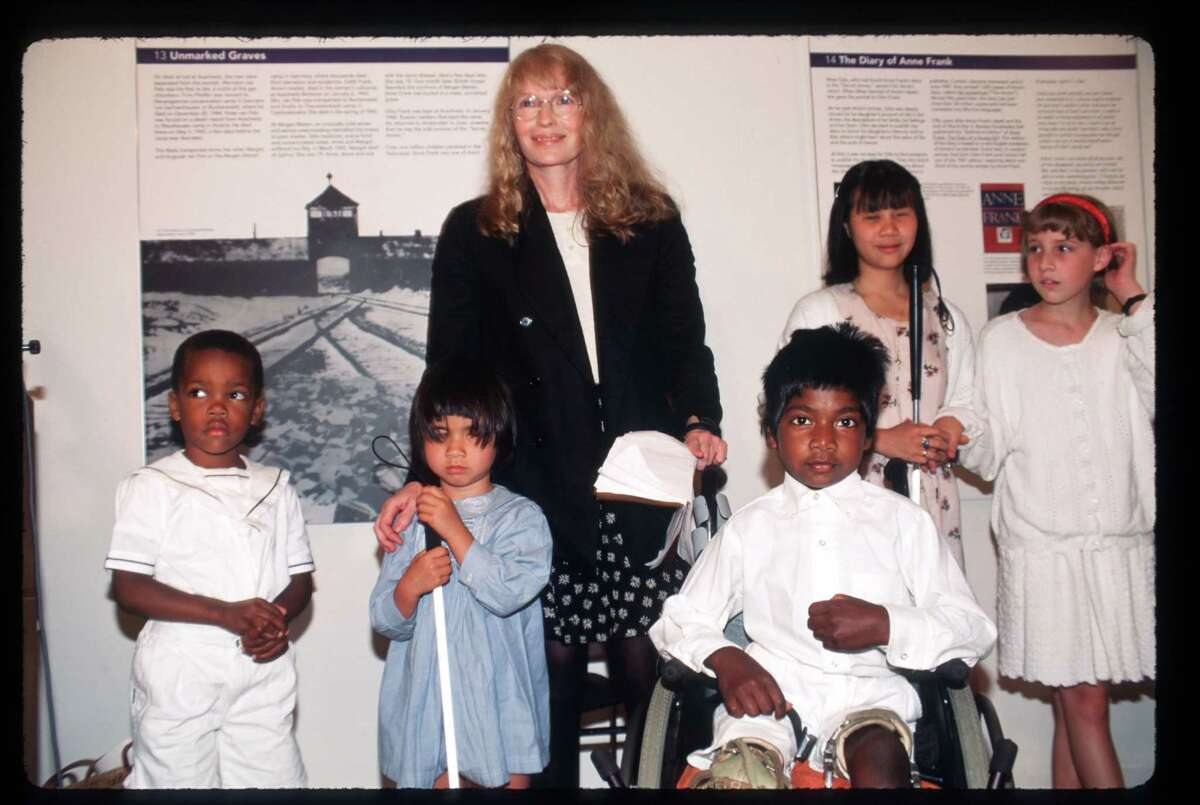 Actress Mia Farrow stands with her children at the Anne Frank Center June 12, 1996 in New York City. Thaddeus Farrow, front in wheelchair, committed suicide Wednesday, Sept. 21, 2016 with a single gunshot wound in a car along Route 67 in Roxbury, Conn.