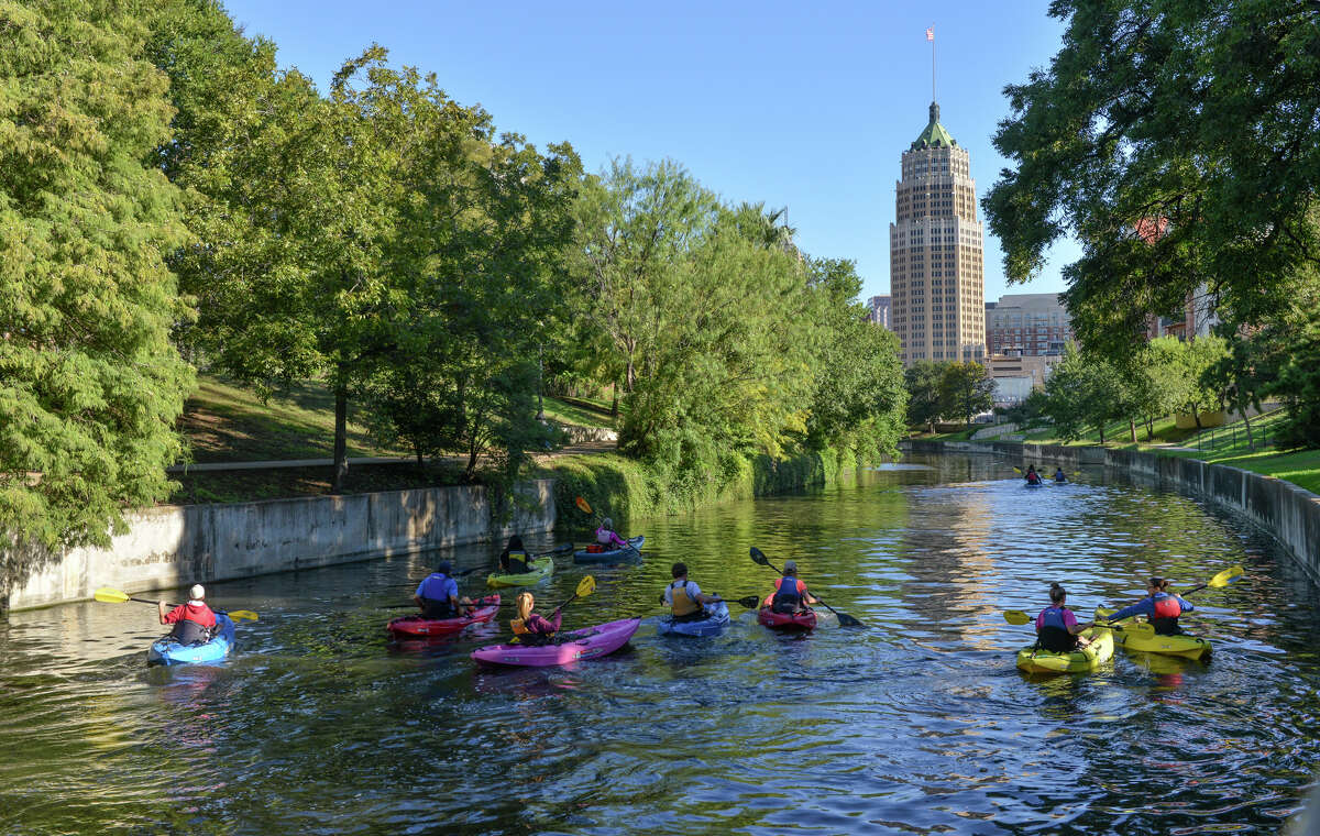 Kayakers paddle along the San Antonio River near the King William District.