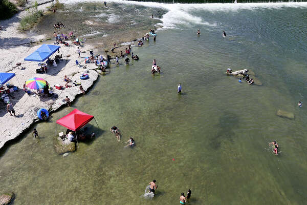 Trying to beat the heat, people cool off in the Guadalupe River at the Faust Street Bridge in New Braunfels.