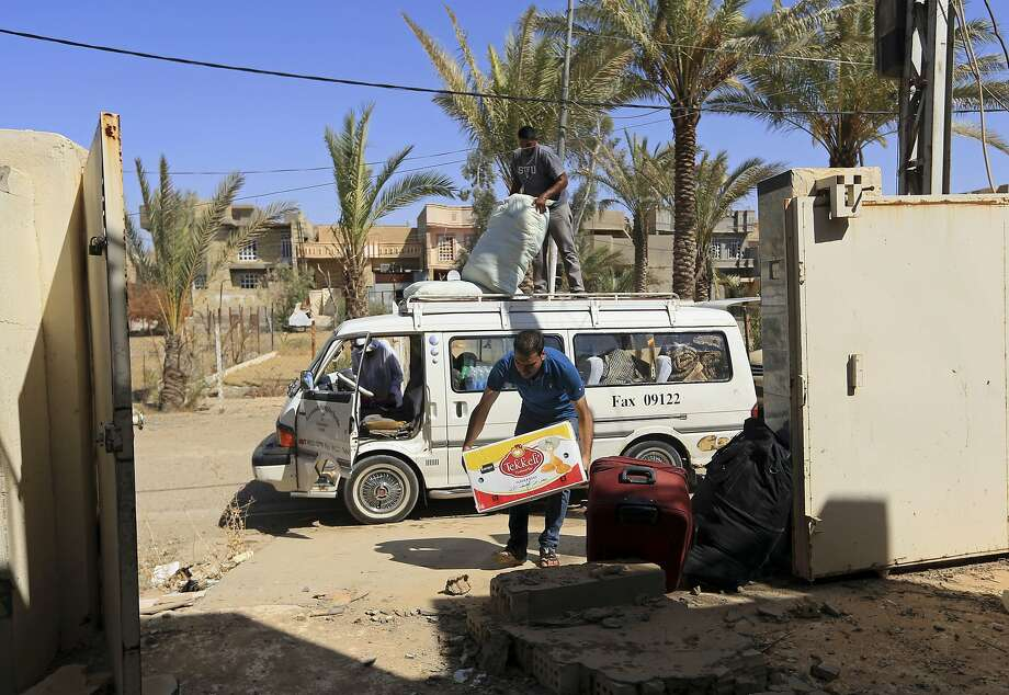 A man unloads belongings in Fallujah. Returnees face stringent security checks before re-entering. Photo: Khalid Mohammed, Associated Press