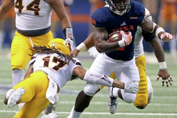 UTSA running back Jarveon Williams looks for room around Arizona State defensive back J'Marcus Rhodes during first-half action on Sept. 16, 2016 at the Alamodome.
