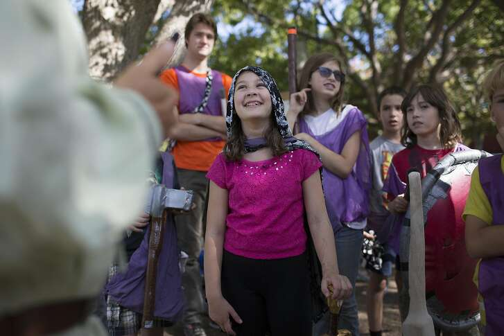 "Caely Orr, 11, smiles as Christopher Melville explains some rules to a group of young LARPers at Mitchell Park on Wednesday, September 21, 2016 in Palo Alto, Calif. ""I love to get invested in the characters and the back stories,"" says Orr."