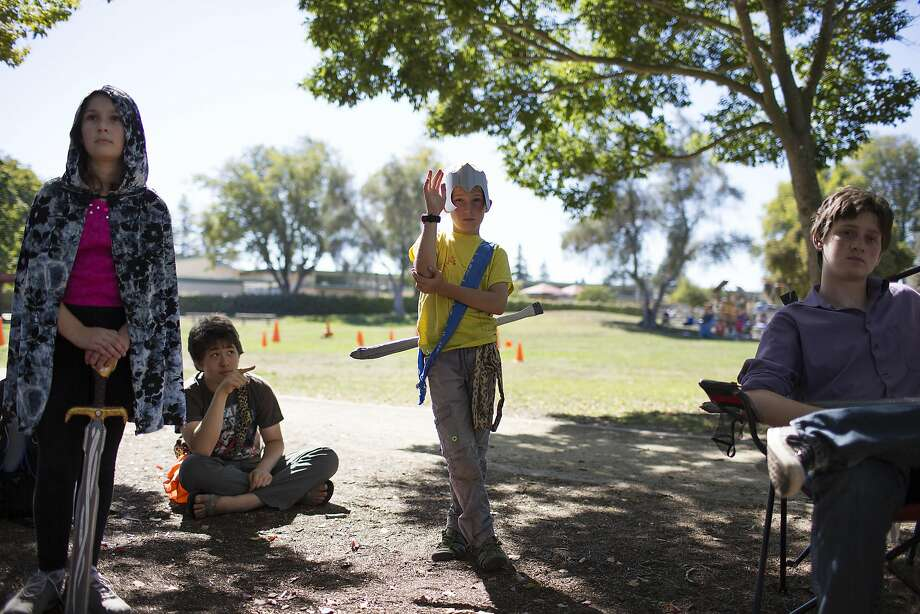 Anton Komarov, 10, center, raises his hand to make a suggestion during the start of a LARPing mission at Mitchell Park on Wednesday, Sept. 21, 2016, in Palo Alto. Christopher Melville, who started leading the junior league at the park 10 years ago, says the live-action role playing helps kids develop critical-thinking skills while using their imagination. Photo: Erin Brethauer, The Chronicle