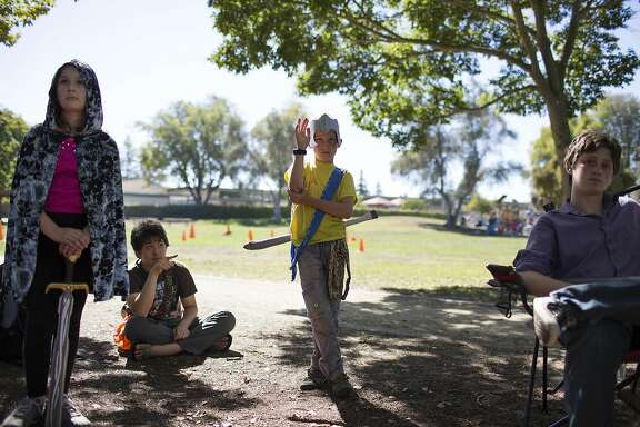 Anton Komarov, 10, center, raises his hand to make a suggestion during the start of a LARPing mission at Mitchell Park on Wednesday, September 21, 2016 in Palo Alto, Calif. Christopher Melville, who started leading the junior league at the park 10 years ago, says the live-action role playing helps kids develop critical thinking skills while using their imaginations.