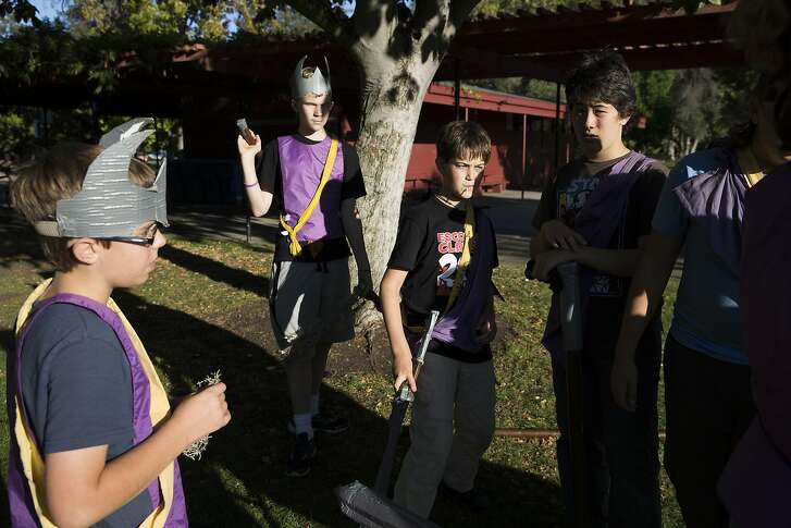 A group of young LARPers gather to discuss a mission at Mitchell Park on Wednesday, September 21, 2016 in Palo Alto, Calif.