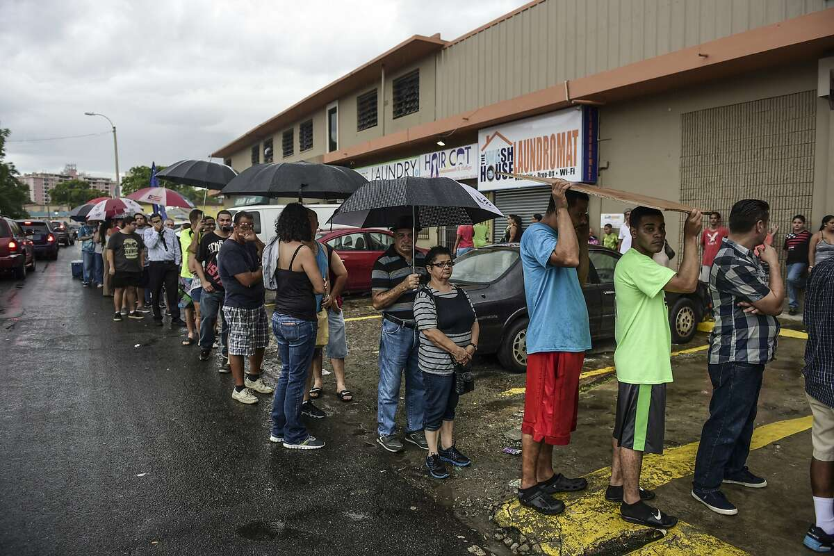 People wait in line to buy ice during a massive blackout in San Juan, Puerto Rico, Thursday, September 22, 2016. Puerto Ricans faced another night of darkness Thursday as crews slowly restored electricity a day after a fire at a power plant caused the aging utility grid to fail and blacked out the entire island. (AP Photo/Carlos Giusti)