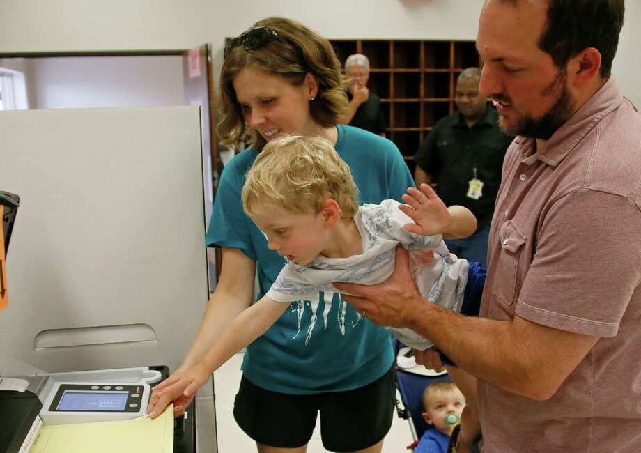 Oklahoma parents show their son democracy in action during early voting. Whether states are complying with Voter ID educational requirements should be determined by courts of law, not debates in the public arena, a reader says. Photo: Sue Ogrocki /Associated Press / AP2016