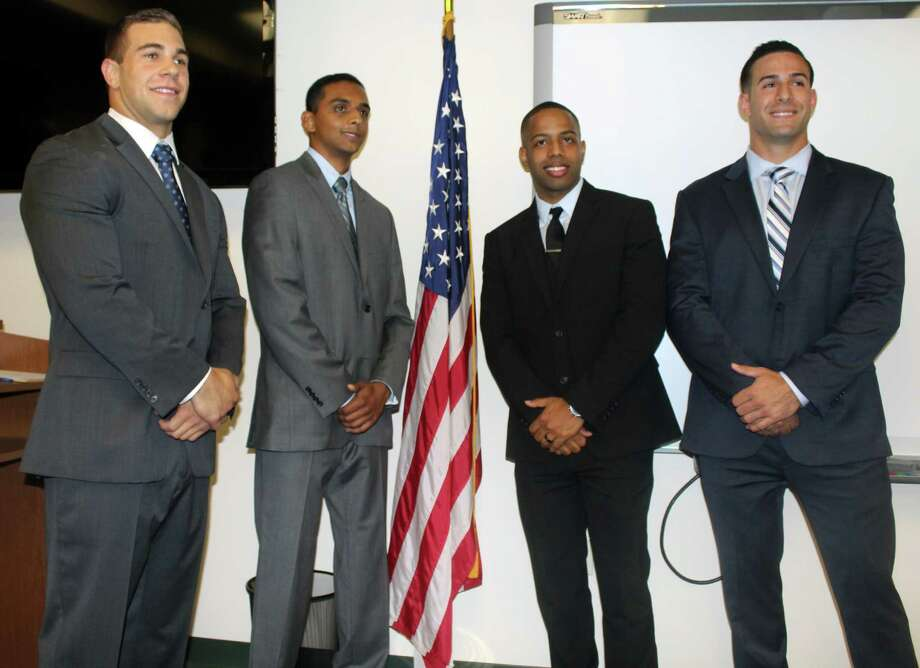 From left, Louis Gannon, Neil Nair, Jeffrey Brown and Joseph Cusano were sworn in to the Darien Police Department on Monday. They begin police academy training on Oct. 3. Photo: Erin Kayata / Hearst Connecticut Media / Darien News