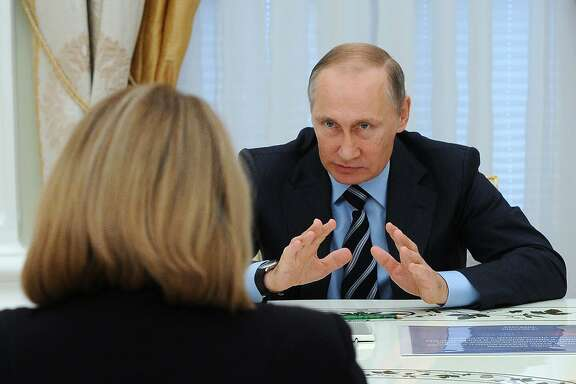 Russia's President Vladimir Putin (R) gestures during a meeting with the Head of the Central Election Commission (CEC) Ella Pamfilova and CEC members at the Kremlin in Moscow on September 23, 2016. Russian President Vladimir Putin on September 23 bumped a key Kremlin official who oversaw a crushing victory for the ruling party at polls last week to parliament speaker, as he continued to shuffle top posts. / AFP PHOTO / Sputnik / Mikhail KLIMENTYEVMIKHAIL KLIMENTYEV/AFP/Getty Images