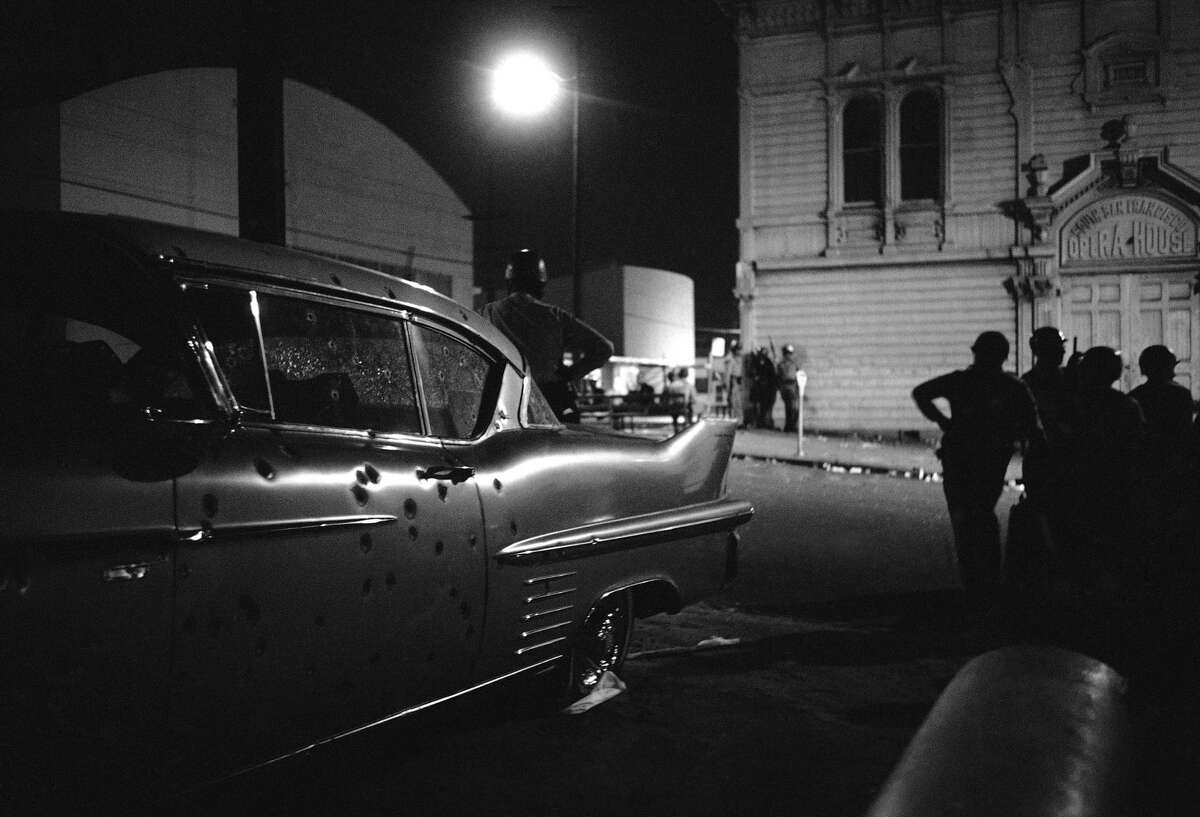 FILE -The bullet-riddled car in foreground is mute evidence of fire fight between a black sniper and police at Newcomb and Mendell Streets Bay View-Hunters Point area in San Francisco, Sept. 29, 1966. The sniper, police said, was wounded. In the background is South San Francisco's Opera House. (AP Photo/Robert W. Klein)