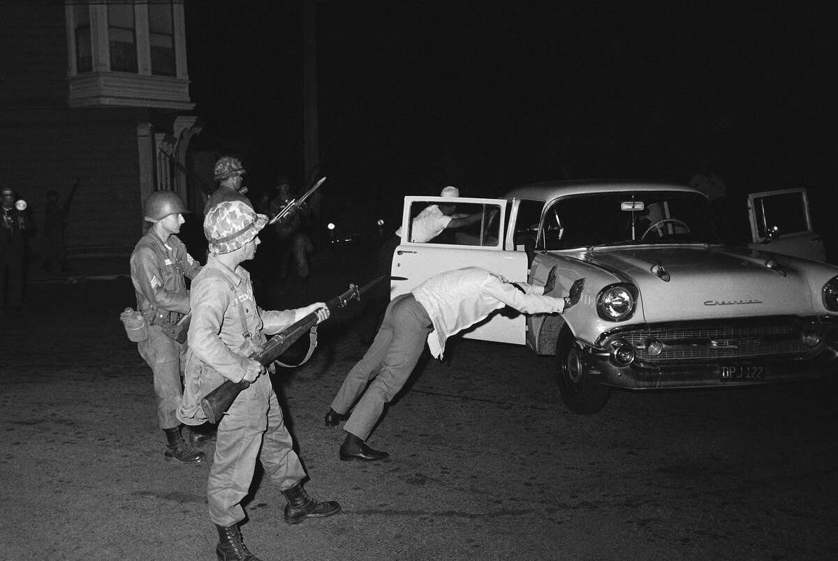 FILE - Two black occupants of this car are held at bay by California National Guardsmen with fixed bayonets in the Hunters Point riot area of San Francisco, Sept. 28, 1966. The car was stopped when it was suspected of carrying guns and ammunition. The area was secured by Guardsmen who imposed curfew. (AP Photo/Robert H. Houston)