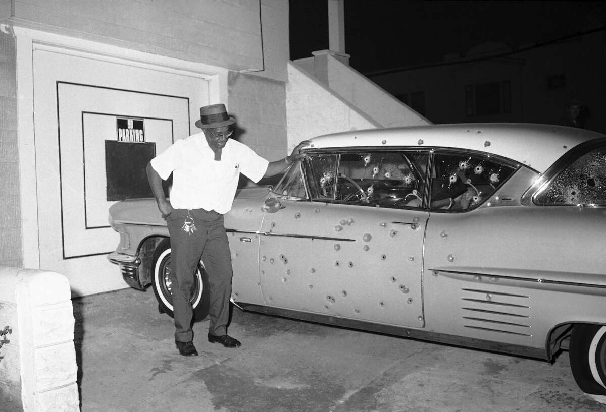 FILE -Howard Bacon, 54, of 1600 Newcomb St., San Francisco, was standing on the porch of his home when a black sniper jumped behind his car and started firing at police in San Francisco, Sept. 28, 1966. They responded in kind and Bacon sadly looks at his damaged auto. The shooting took place near Third and Newcomb Streets in San Francisco's Bay View and Hunters Point riot area. (AP Photo/Robert H. Houston)