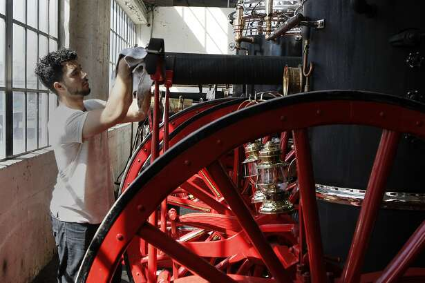 CCSF Fire Academy student Mohammad Malik cleans a 1897 Clapp & Jones Steam Engine at Pier 45 in San Francisco, Calif. on Friday, September 23,  2016.