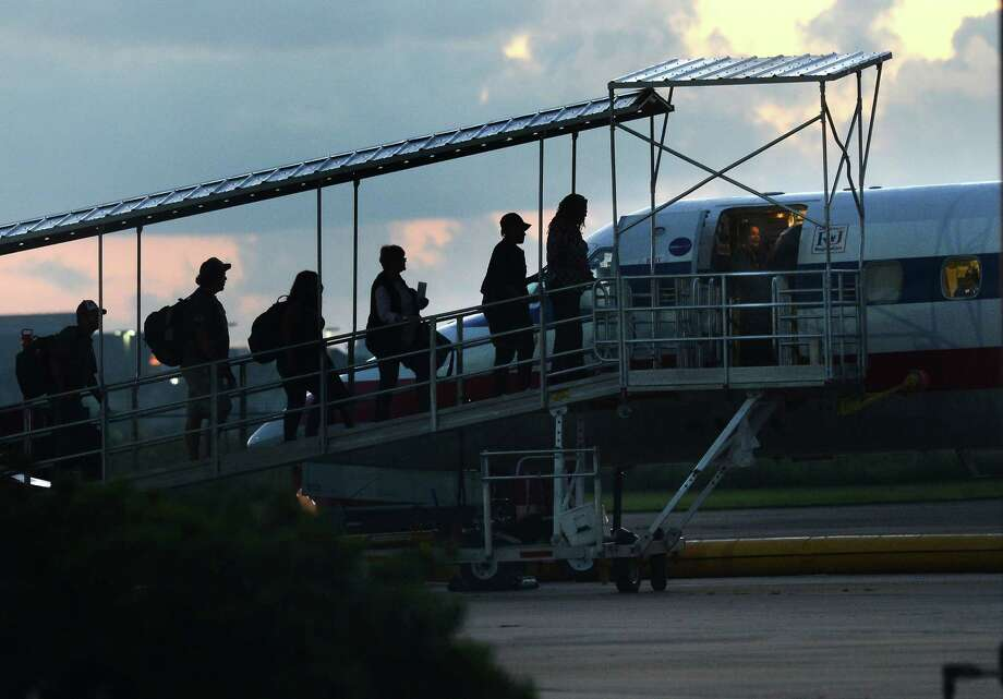 Passengers board an American Airlines flight at the Jack Brooks Regional Airport early Thursday morning. In recent months, several passengers were bumped from their flight due to the weight limitations of using the airporté•s shorter, secondary runway. Construction on the primary runway was finished Tuesday and regular traffic is expected to continue.  Photo taken Thursday, September 22, 2016 Guiseppe Barranco/The Enterprise Photo: Guiseppe Barranco, Photo Editor