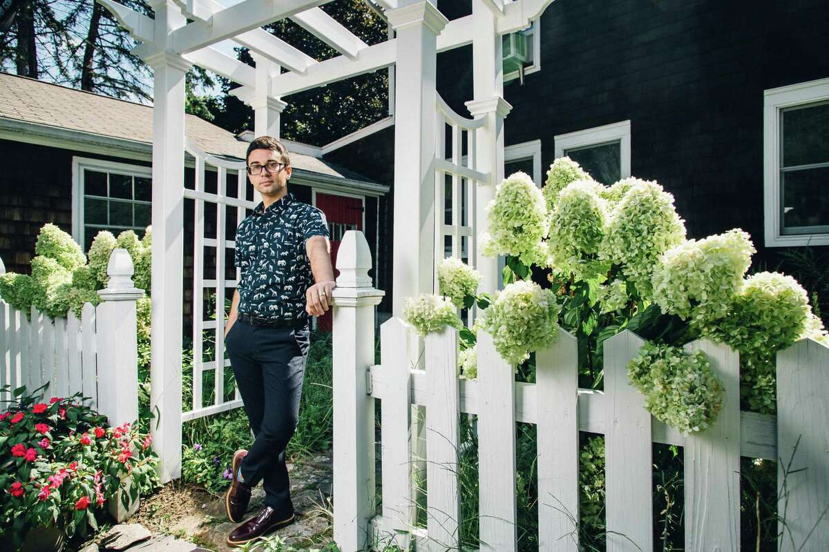 Fashion designer Christian Siriano stands at the gate of his home in Danbury, where he chose to have his recent wedding.
