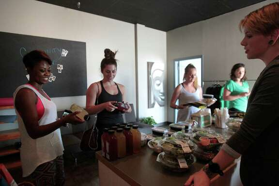 Brittany Crocker, traveling general manager for Snap Kitchen talks with Tosha Evans, Cori Scherer and Megan Horton at Yin Yoga, 3938D North Shepherd Drive after a lunchtime class that provided a free Snap Kitchen salad after the yoga class, Tuesday, Aug. 23, {year}, in Houston. ( Karen Warren / Houston Chronicle )