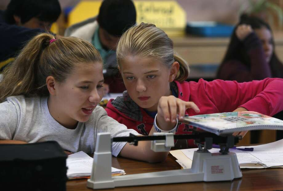 Above: Lilly Weires (left) and Abby Delanoy practice using a scale in Melanie Bernal's seventh-grade science class at Sequoia Middle School in Pleasant Hill. Top: Students construct paper roller coasters for marbles in a hands-on technology class at Sequoia Middle School. Photo: Paul Chinn, The Chronicle