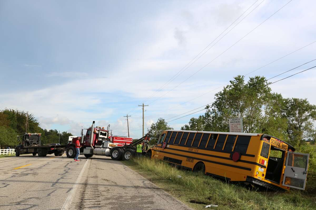 A crew tries to move the school bus that crashed at FM 1942 and Bohemian Hall on Friday afternoon.