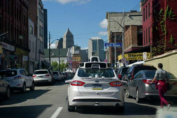 Ford Fusions modified by Uber for autonomous use map out the streets of Pittsburgh ahead of the launch of its driverless system. New rules of the road for robot cars coming out of Washington this week could lead to banning human drivers.