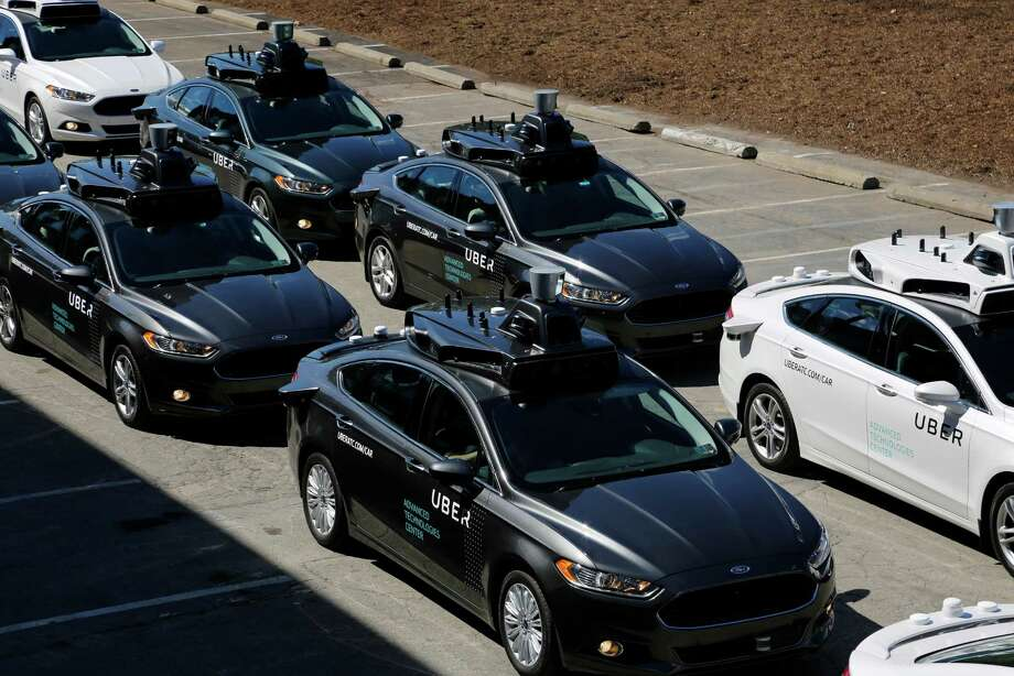 """A group of self-driving Uber vehicles position at Uber's Advanced Technologies Center in Pittsburgh. Regulators are accelerating the shift to robot drivers with new rules that will provide a path for going fully driverless by removing the requirement that a human serve as a backup. Earlier this year, the National Highway Traffic Safety Administration recognized Google's self-driving software as the """"driver"""" in its fully autonomous test vehicles, eliminating the need for a person to be present. Photo: Gene J. Puskar /Associated Press / AP"""