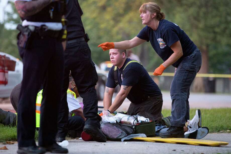Members of the Chicago Fire Department work on a gunshot victim at the scene of a double shooting in Ogden Park on Sept. 5. Could this have been prevented if police devoted more resources to shootings in which no one is wounded or killed? Photo: Erin Hooley /Associated Press / Chicago Tribune