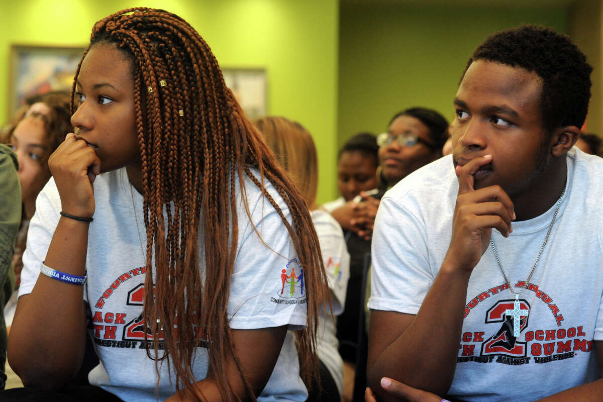 Ryanna Johnson and Caled Bailey, students at Fairchild Wheeler Interdistrict Magnet School, listen to speakers at the Back to School Youth Summit, held at Housatonic Community College in Bridgeport on Friday.