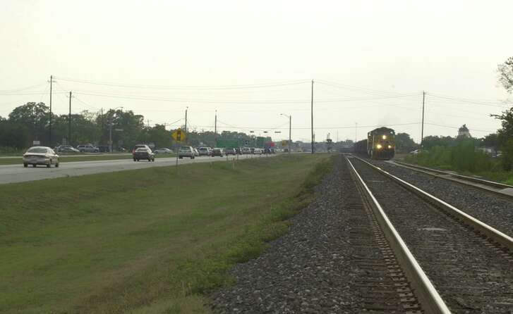 Cars traveling on U.S. 90A during rush-hour traffic in 2006, where a grass section has been sitting for Metro's planned commuter rail line for years..