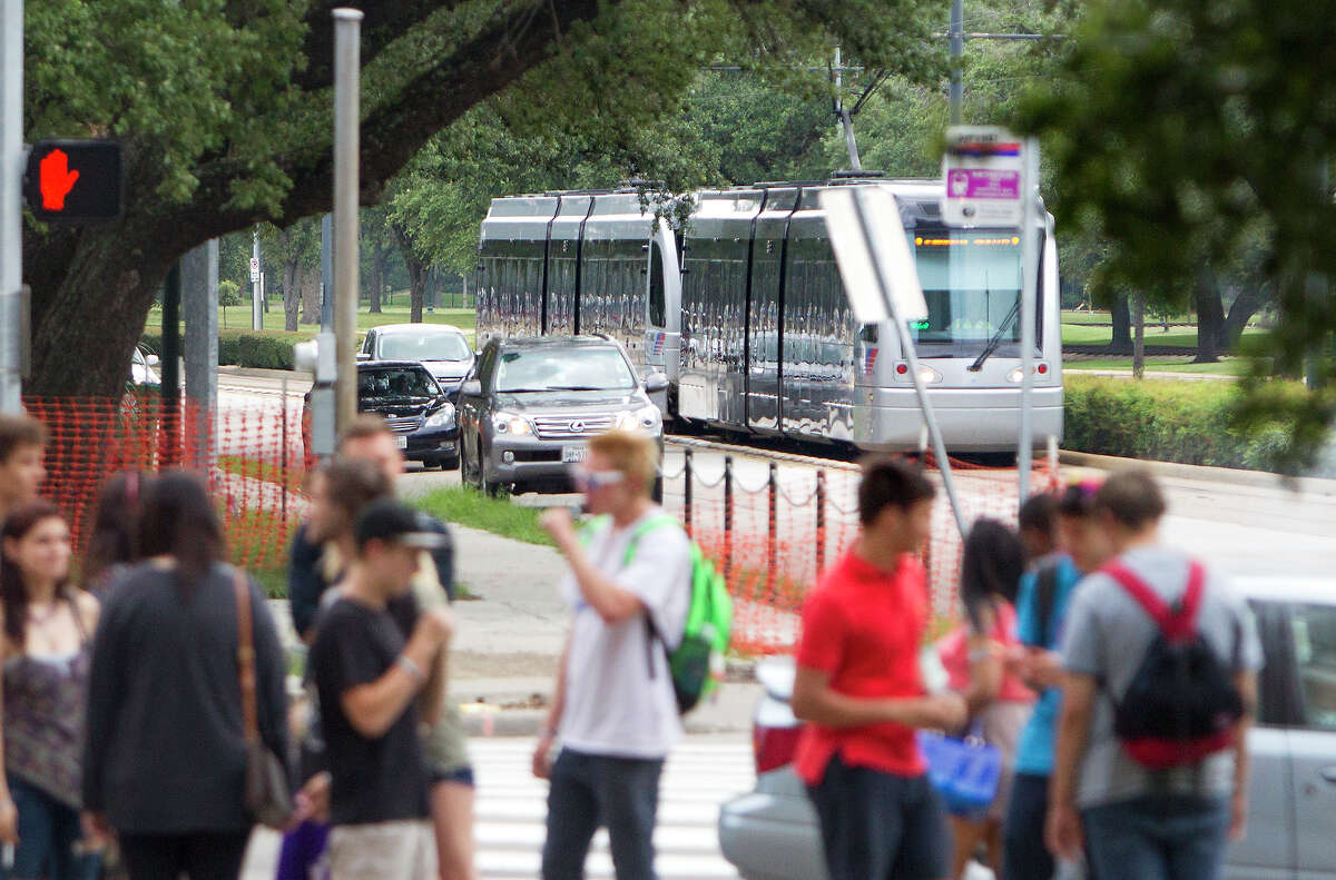 A Metro train makes its way along the track as a group of pedestrians stand on the corner of Cambridge Drive near Fannin Street in the Texas Medical Center, on July 24, 2014.