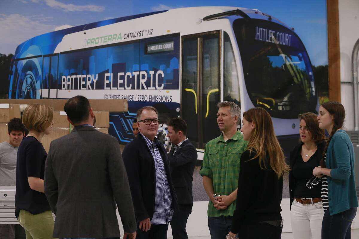 Members of engineering team gather at the headquarters of Proterra, an electric bus company at its headquarters in Burlingame, Calif., as seen on Thurs. September 22, 2016. A photo of their Catalyst XR electric bus covers a wall in the background.