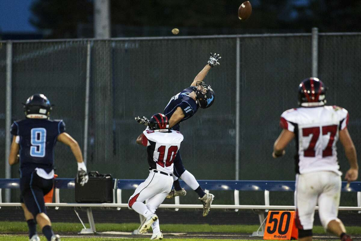 Meridian High School senior Taylor Woodcock attempts to make the catch while being defended by Beaverton High School senior Marcus Eberlein in a game at Meridian High School on Friday.