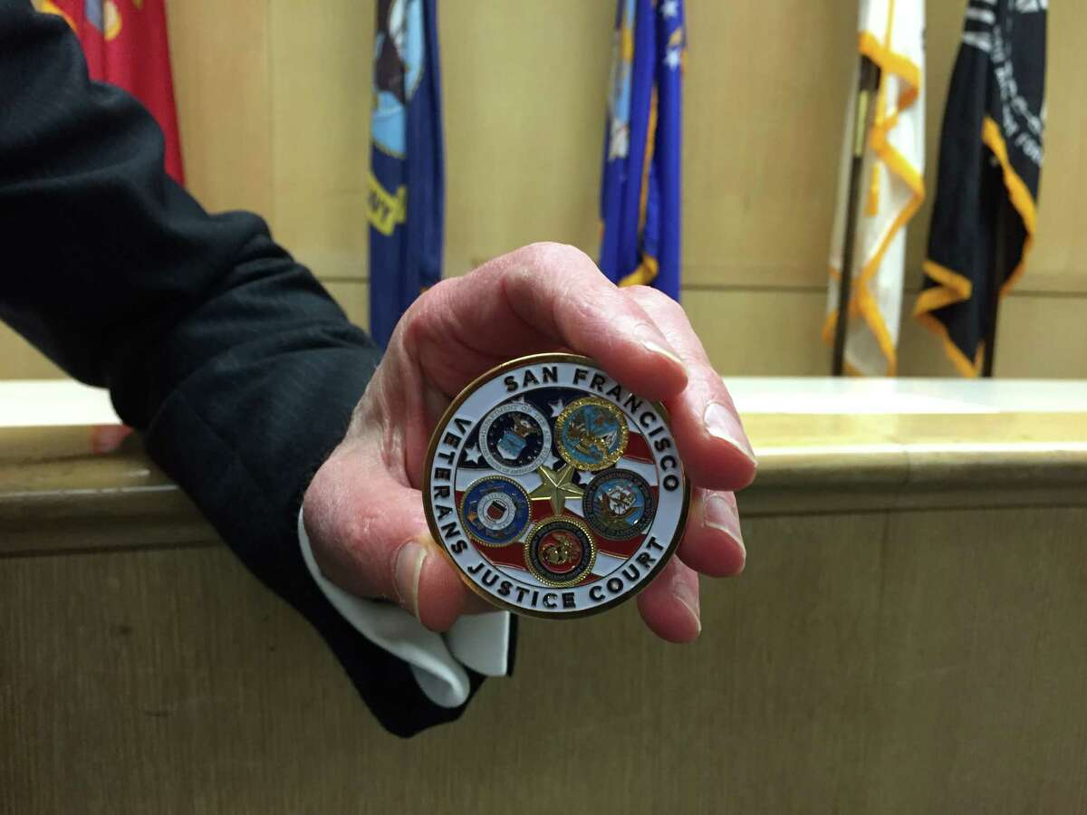 Judge Jeffrey S. Ross rewarded veterans who completed the Veterans Justice Court program with a certificate and a commemorative coin.