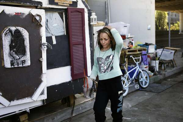 """Krystal Gaither cleans an area outside her """"box"""" home at a homeless encampment along 7th Street on Friday, September 23,  2016 in San Francisco,  California."""
