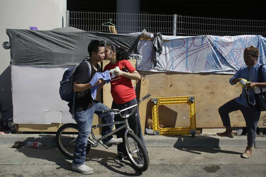 As he heads to work, Ruben Calalo (left) gets a kiss from partner Aliren Sunga at the Box City encampment on Seventh Street. The couple are part of a group of immigrants who know each other from the Philippines. Photo: Lea Suzuki, The Chronicle