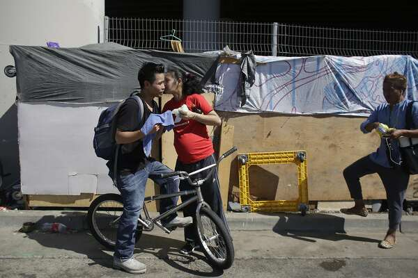 Ruben Calalo (l to r) gets a kiss goodbye from his wife Aliren Sunga as he heads off to work from a homeless encampment along 7th Street on Friday, September 23,  2016 in San Francisco,  California.