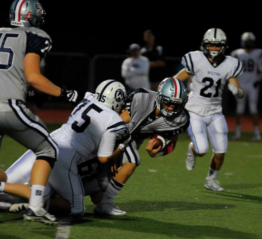 Staples' Harris Levi, center, drags tacklers as he runs during a game against Wilton on Friday, September 23rd, 2016. Photo: Ryan Lacey/Hearst Connecticut Media / Westport News Contributed