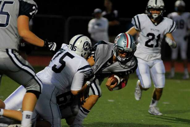 Staples' Harris Levi, center, drags tacklers as he runs during a game against Wilton on Friday, September 23rd, 2016.