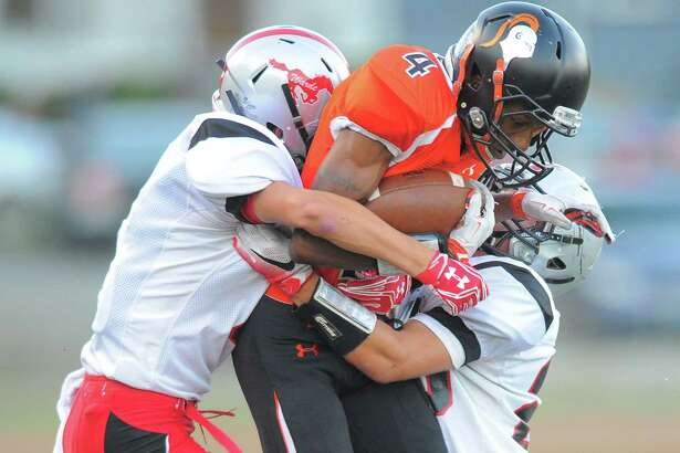 Stamford's Rich Scott is brought down by a pair of Warde defenders on Friday night at Boyle Stadium.